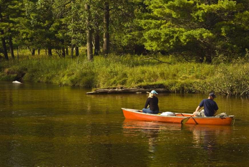 man and woman paddling an orange canoe on river