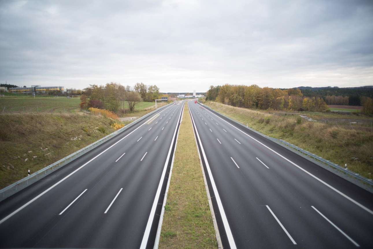 three lane highway in countryside disappearing into the distance