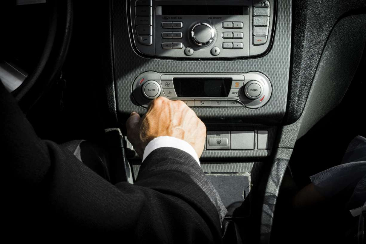 man in black suit driving and adjusting controls on dashboard
