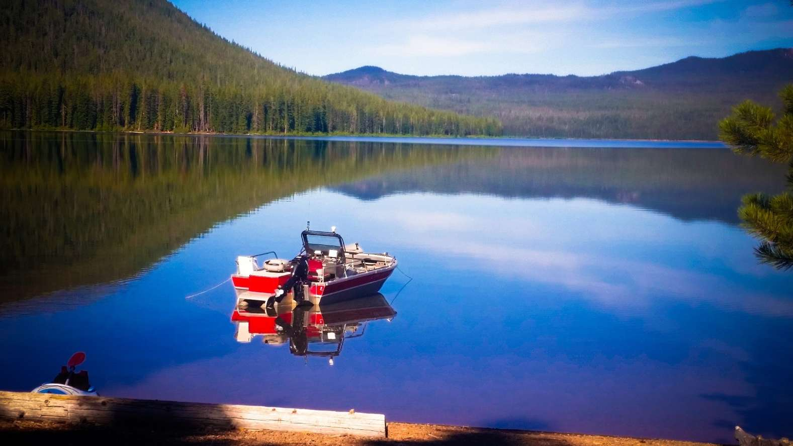 red and white boat in still lake surrounded by forested mountains