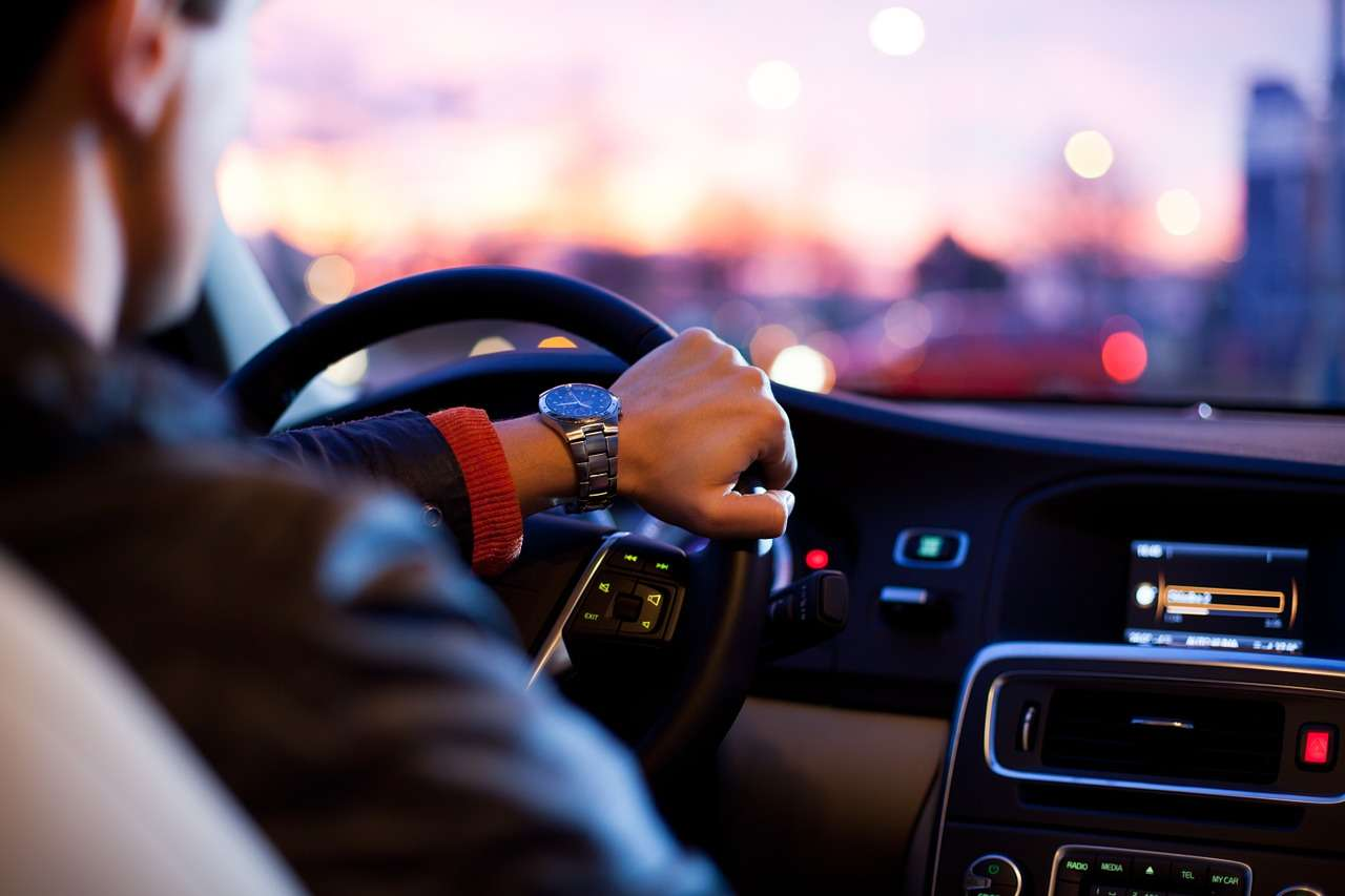 man in leather jacket driving through city at sunset